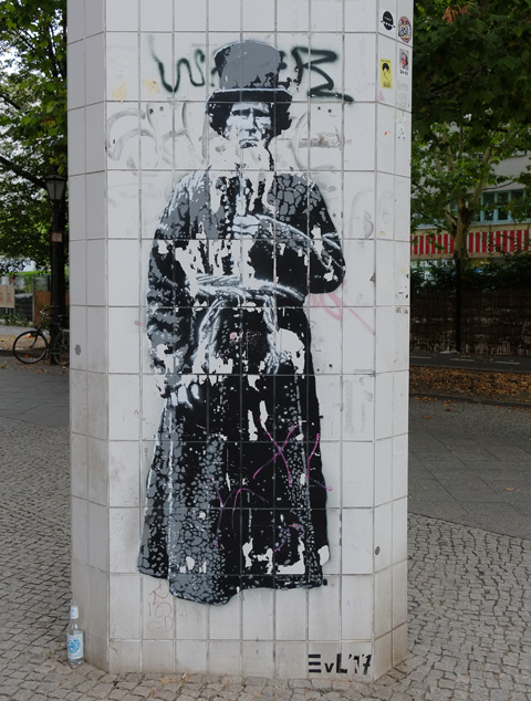 on a pillar in Wedding Berlin, an almost life sized in shades of grey, street art of a person that looks like Abraham Lincoln in a long robe