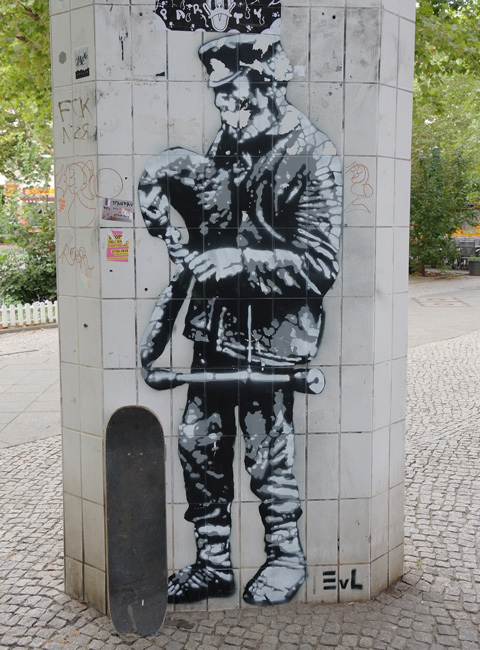 on a pillar in Wedding Berlin, an almost life sized in shades of grey, street art of a person, working man in jeans and jacket
