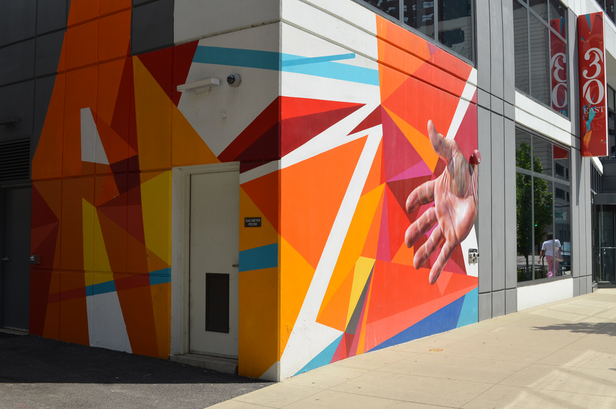 on the corner of a building, on both sides, a mural in bright oranges and reds, sharp edges, linear, with a realistic hand as well,