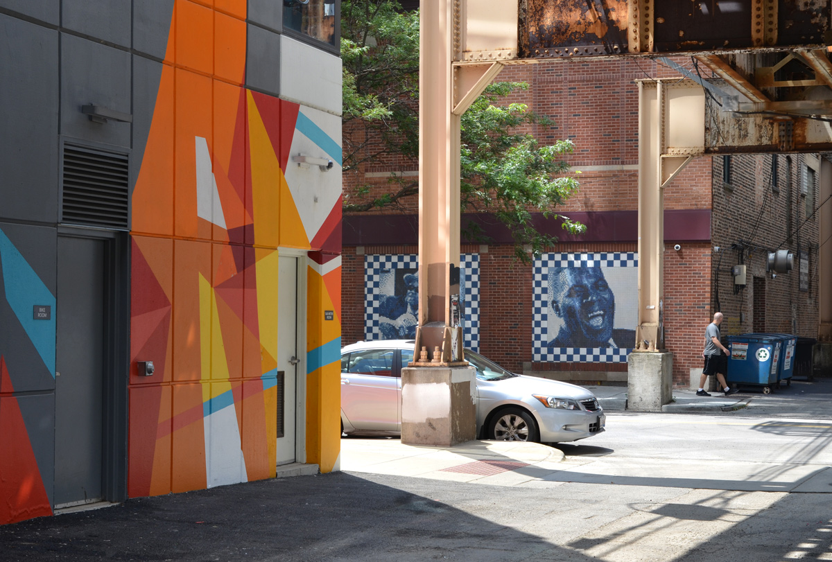 mural in bright oranges and reds, sharp edges, linear, and across the street are portraits of musicians done in tile shaped pieces