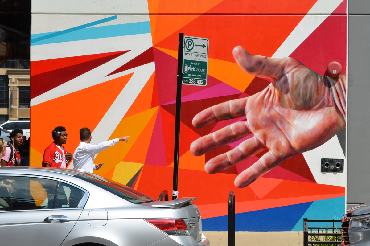 mural in bright oranges and reds, sharp edges, linear, with a realistic hand as well, people walking past it, one man with hand out pointing at something