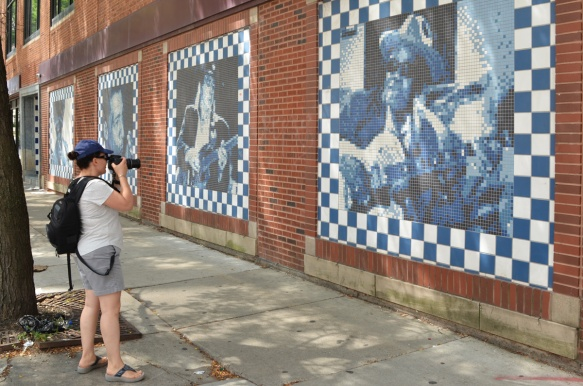 carol taking a picture of a row of murals of black musicians done in little squares on a brick wall in Chicago