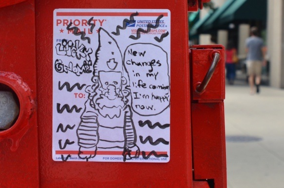 a sticker made with a USA postal sticker, picture of a gnome with words,