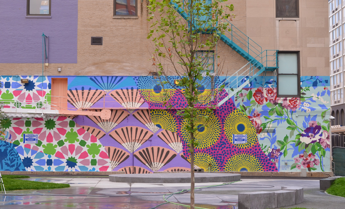 mural by Hello Kirsten on the side of a brick building with a blue exterior metal staircase