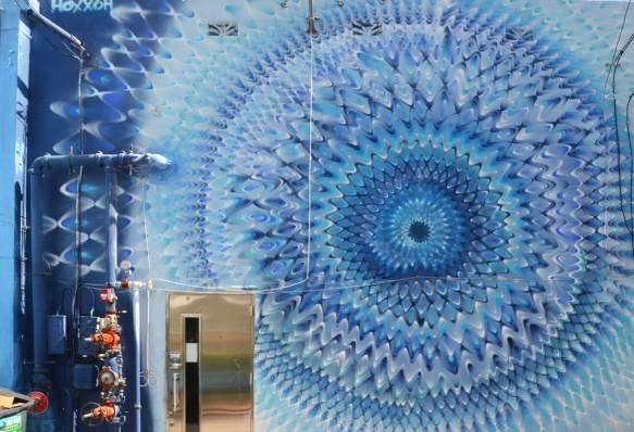 mural by hoxxoh of blue circles or pulsating waves on a wall