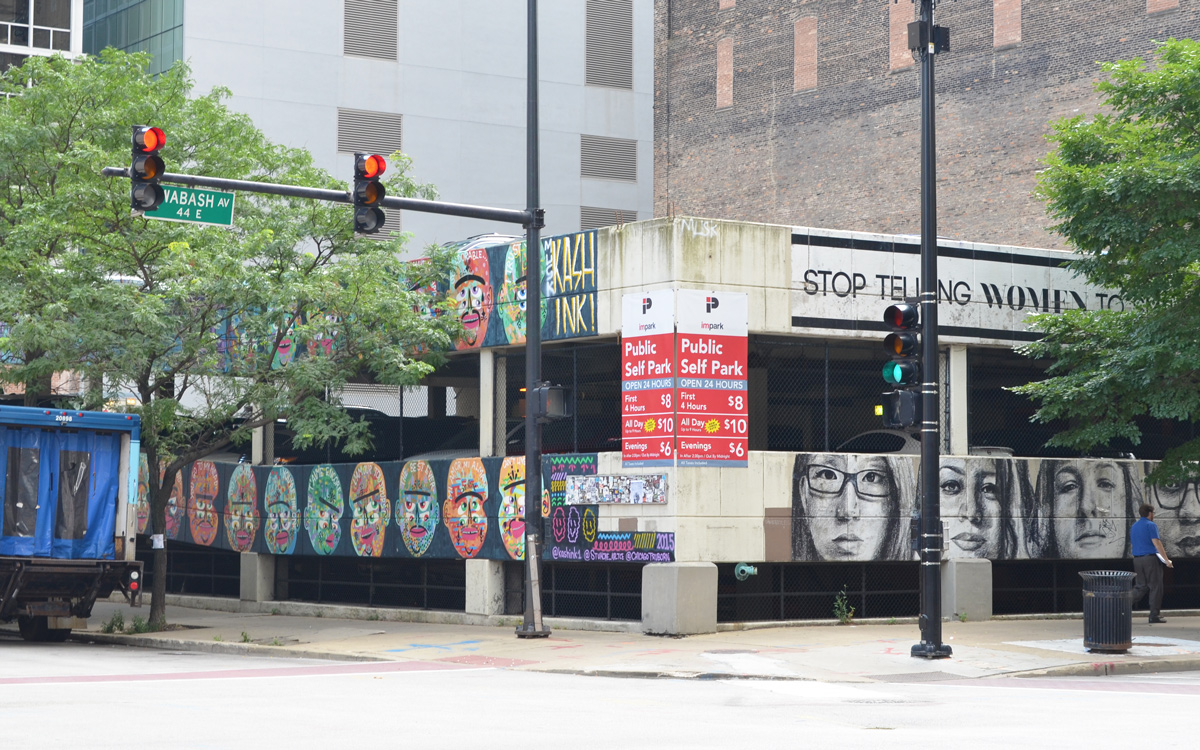 two level parking structure on a street corner in Chicago, the short walls are painted with street art faces. On one side are colourful abstract faces by Kashink and on the other side are black and white faces from the project called Stop Telling Women to Smile.