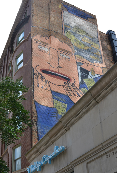 mural on wall above mollys Cupcakes in Chicago, a man with hands by mouth