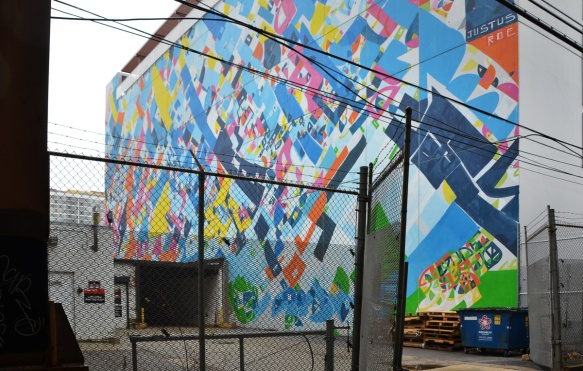 large abstract mural beside a parking lot, small area, also in a fenced in space