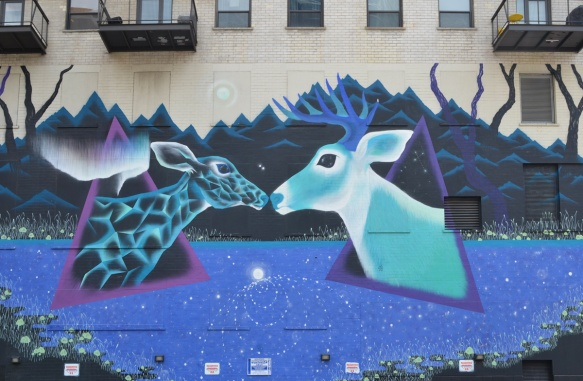 a mural by Marina Zumt of a doe and a buck, two deers, meeting nose to nose, painted in blues and purples