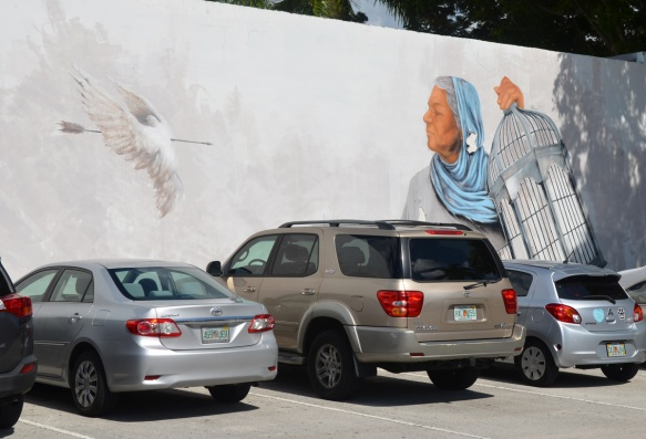 a woman holds open a bird cage for a wounded dove, mural, by evoca1