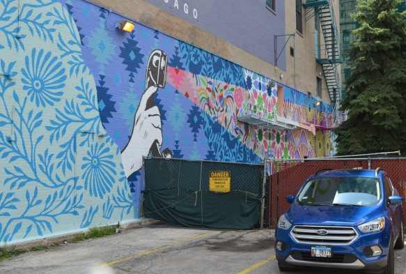 car parked beside a mural, large hand holding an old fashioned telephone receiver but using is as a flashlight