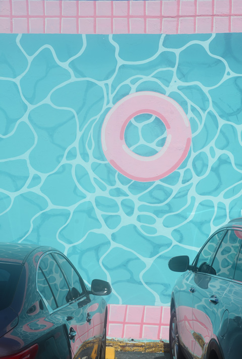 aquamarine coloured water in a mural with pink tile edges on the pool and pink life ring floating in the water