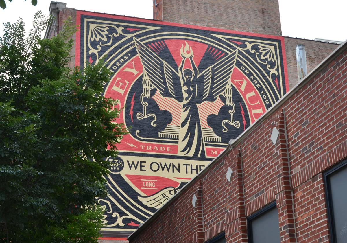 mural by obey in red, black, and gold, on upper storey of a brick building in Chicago