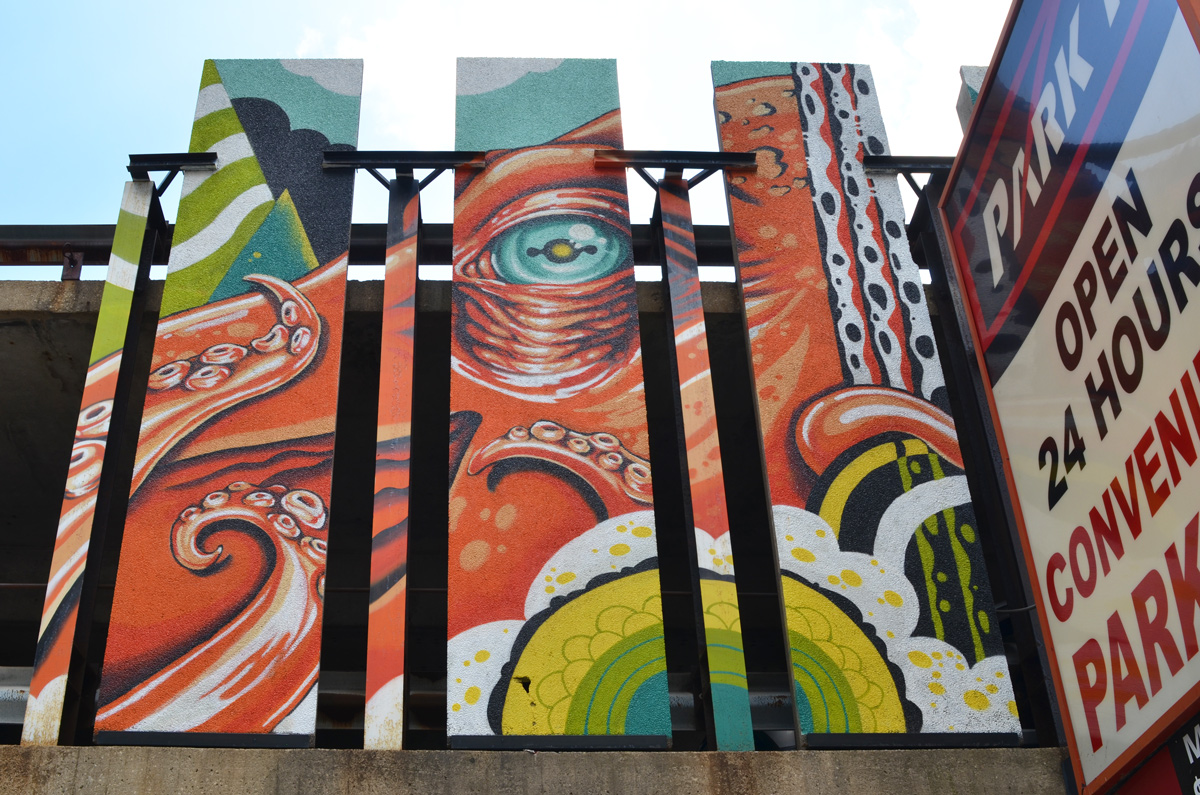 close up of the eye of an orange octopus in a mural by a parking structure