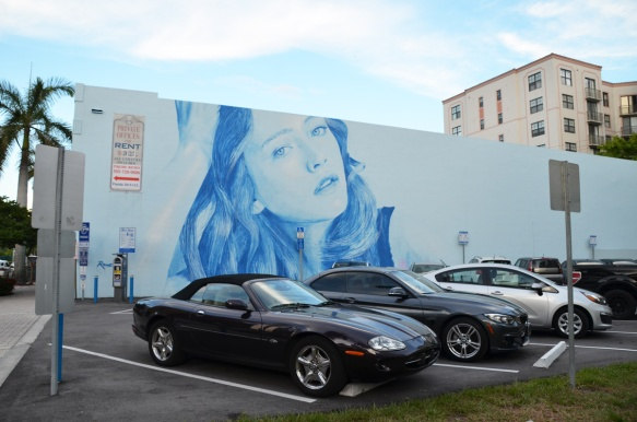 rone mural of a woman's head in blue tones - whole horizontal mural in parking lot with cars parked in front