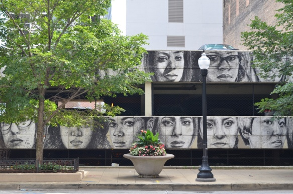 on the walls of a parking structure, a line of realistic faces in grey tones, two rows high