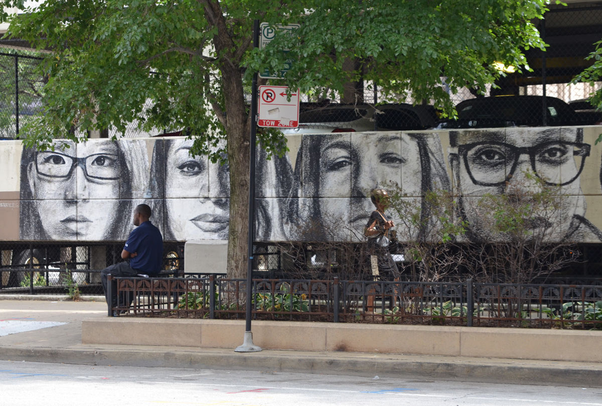 on the walls of a parking structure, a line of realistic faces in grey tones, a man sits on a bench beside it