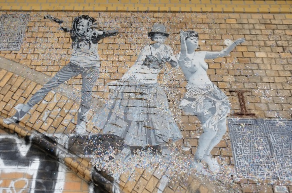 on a brick arch, a paste up in black white, life size picture of people dancing, three women, one in a long skirt, one topless