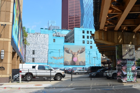 large murals on walls surrounding a parking lot that has an elevated train passing over it