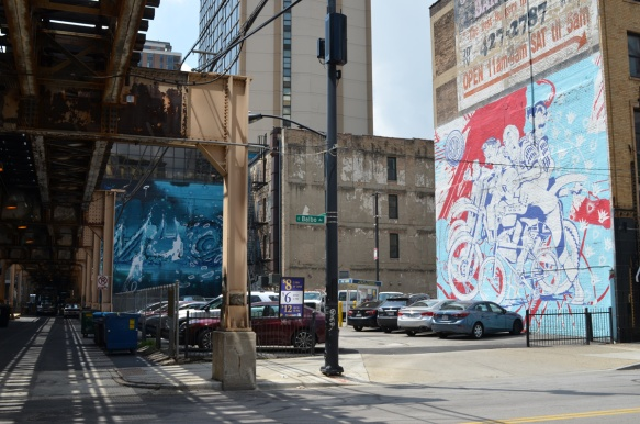 2 murals on Balbao street in Chicago, a blue one by a parking lot and one by asup on the side of a restaurant,