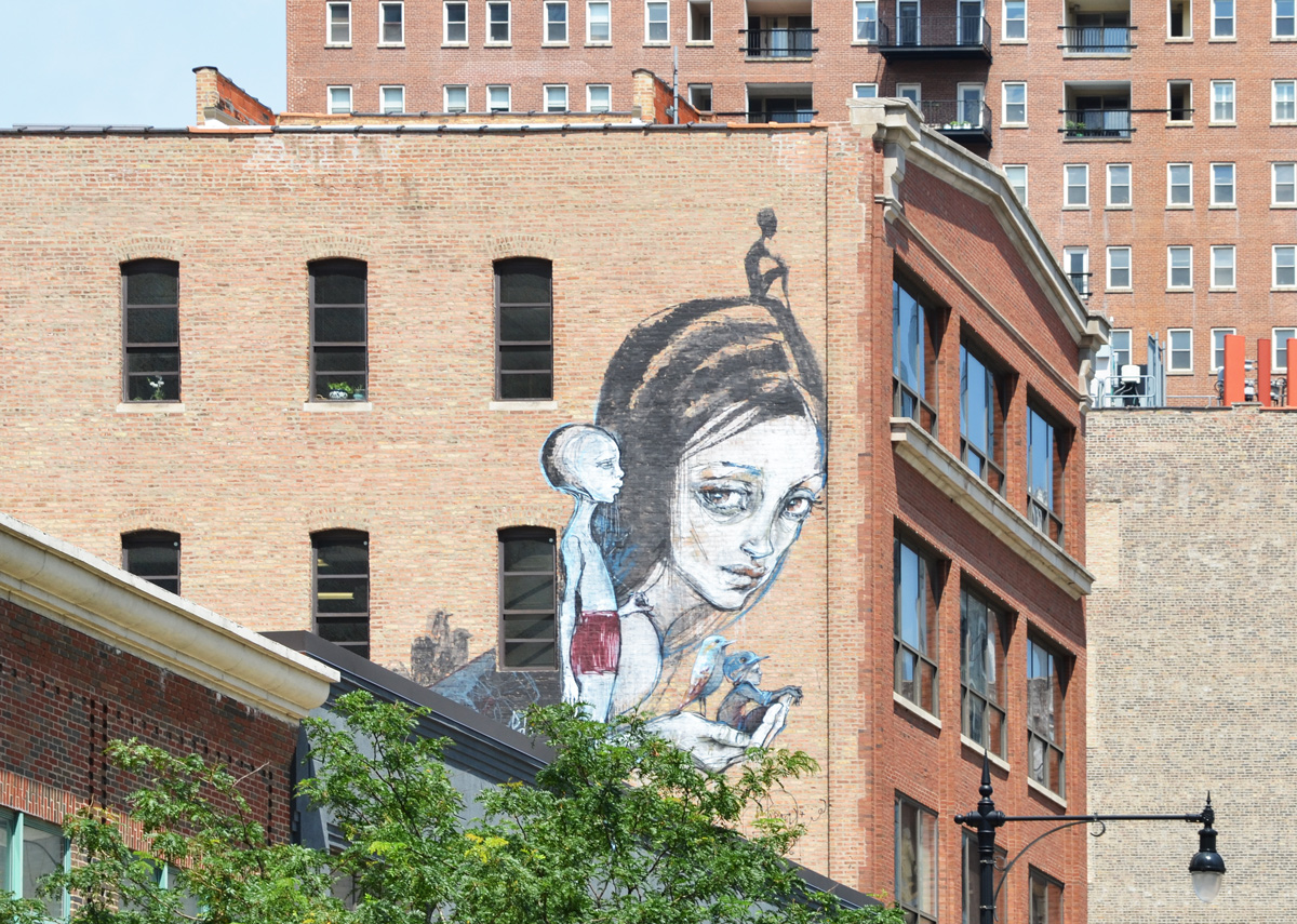 on the upper storeys of a brick building in Chicago, a mural by Hera of a woman holding some birds in her hand, a small white figure stands beside her