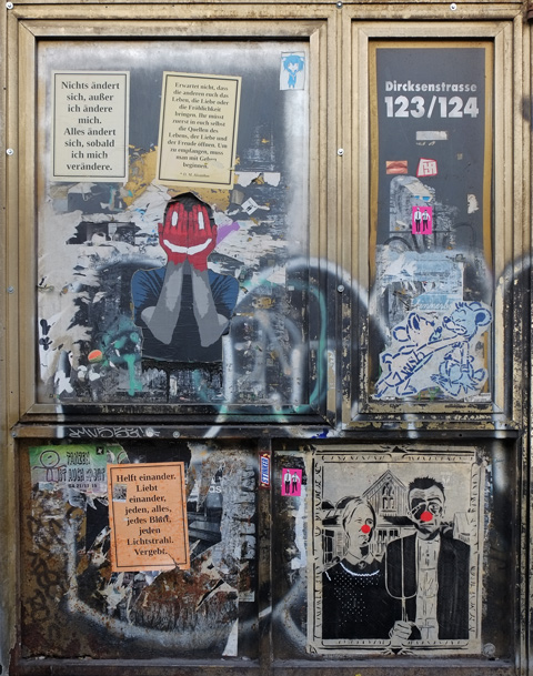 four panes of an old window covered with paste ups and other graffiti.