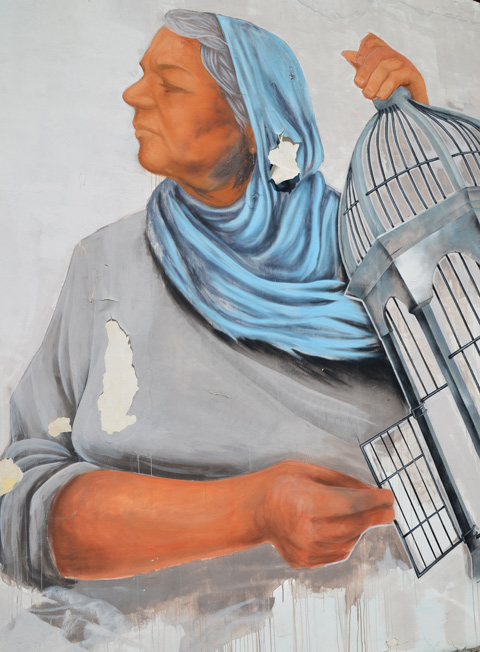 paint peeling on mural, woman in blue head scarf is holding open the door of a bird cage