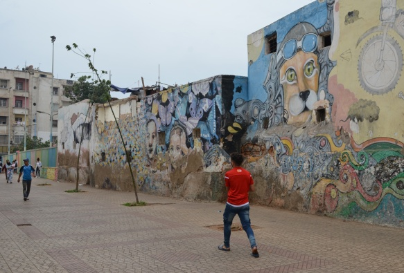 a young man in a red jacket walks past a wall covered with older murals