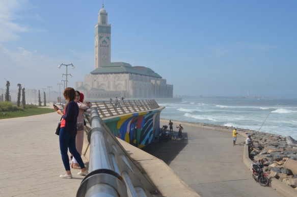 women leaning against railing on path beside the ocean in Casablanca, with Hassan 2 mosque and Atlantic Ocean in the background