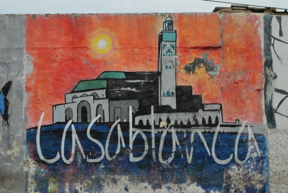 part of a series of murals on a Casablanca wall, the word Casablanca in white with a picture of the Hussan 2 mosque behind it, orange sky at sunset
