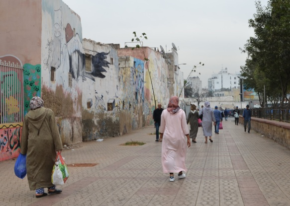 two women in long dresses and head scarves walk past a wall covered with older murals