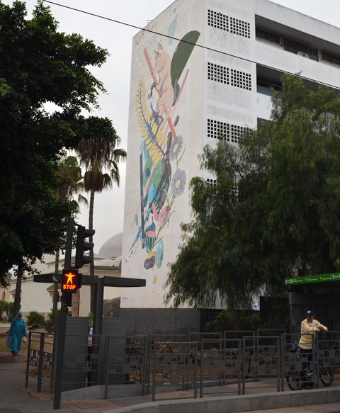 on the side of building, a large mural with a fox, people waiting at a bus stop in front of it