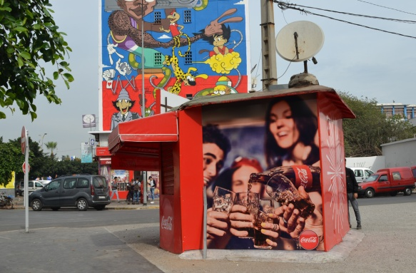 a kiosk covered with ads for coke products in front of a mural of cartoon characters by moka,
