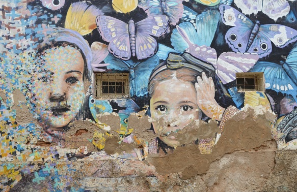 older mural on a wall, little crosses come together to make faces of two girls that are surrounded by butterflies