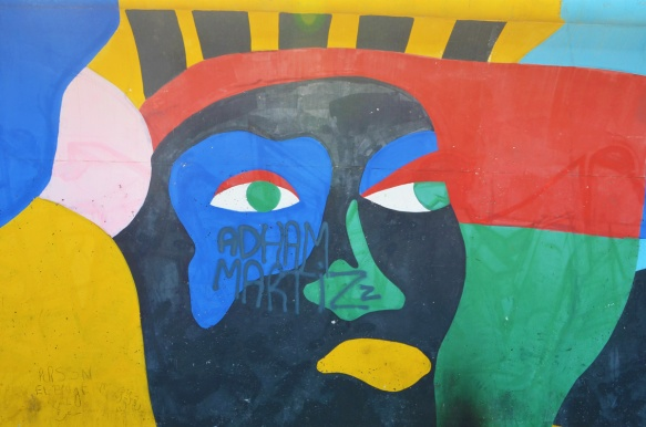 stylized painting of a black face with yellow mouth, blue around one eye, red hair,