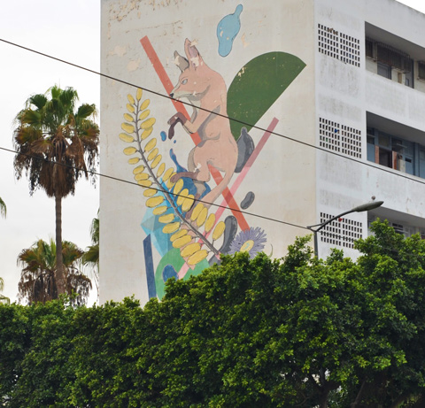 above the greenery of trees, a mural on the side of an apartment building, a foox, yellow leaves, and other pieces of nature