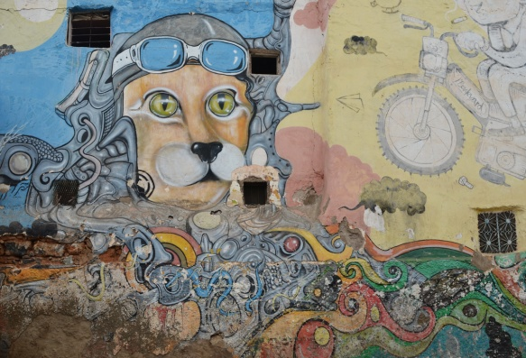 an animal's face with pale green eyes and black nose, with leather helmet and aviator goggles, in a mural