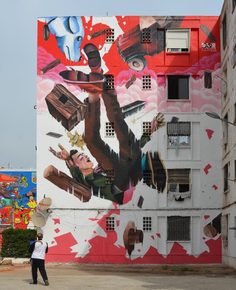 a large vertical mural by oldr of a man falling backwards past pink and white clouds. Falling with him is a blue dog, a car, and some logs