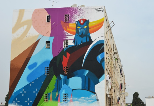 in a residential area of apartment buildings, a large mural by med, closer look