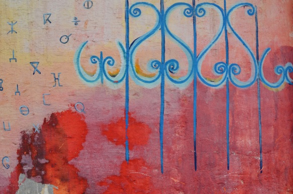 part of a series of murals on a Casablanca wall, in blue curly shapes as seen on many metal railings in Morocco, on a red and orange background
