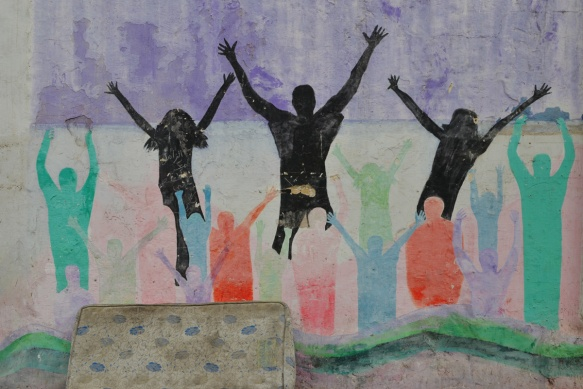 an old mattress sits in front of a mural of silhouette people shapes jumping, in black as well as red, green, and blue people