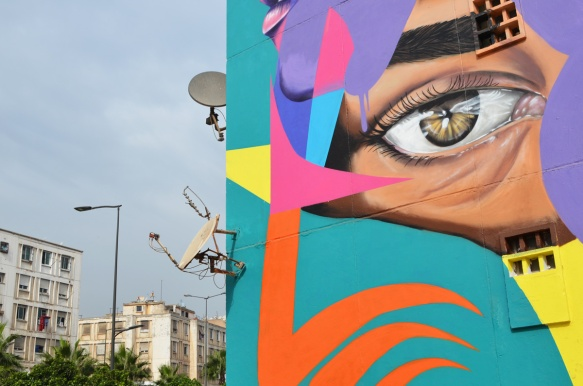 close up of eye in mural with satelite dishes on the building