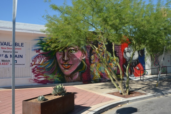 three murals in a row by Nicholai Khan, with #thinkvegas written by them, a woman's face, Charlie Chaplin, and Mickey Mouse