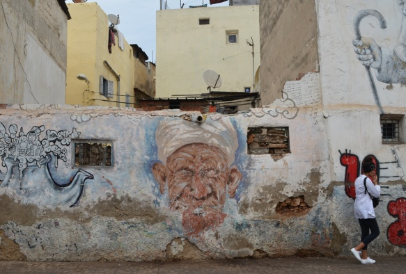 mural on old wall of an old man's head, wearing a white turban