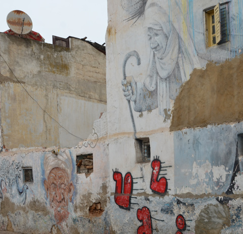 older murals of a man and a woman walking with a cane