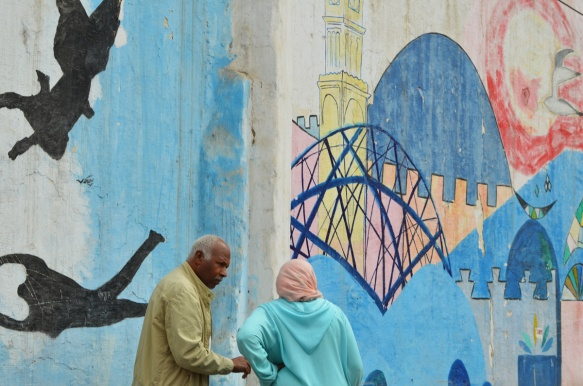 a man and a woman talking to each other as they stand in front of a wall covered in a series of murals