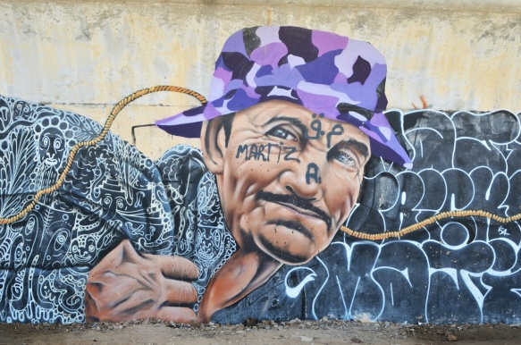 man's head, mural, wearing a purple camo hat and a black top with lots of white squiggles on it. A rope winds its way through the image