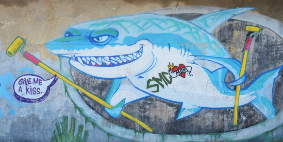 mural of a shark with toothy grin, words that say I want a kiss. Shark is holding a broom, has smd written on chest, as well as a red heart with word mom on it