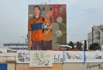 large mural by bakr of a young man in an orange blue T shirt holding a soccer ball or football, bottom part of mural is behind a fence