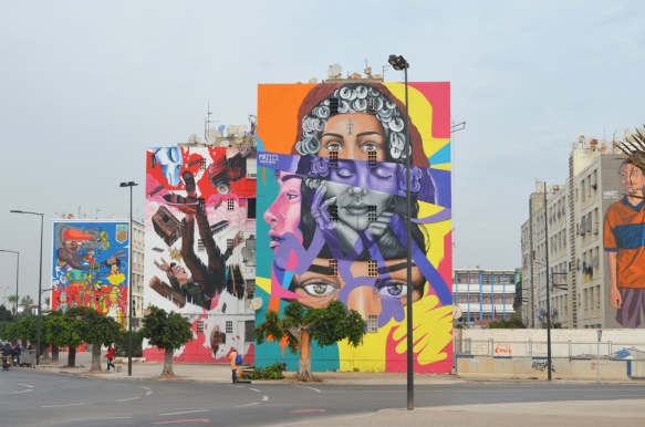 3 large murals at a Casablanca intersection, one in front is woman with many layered face